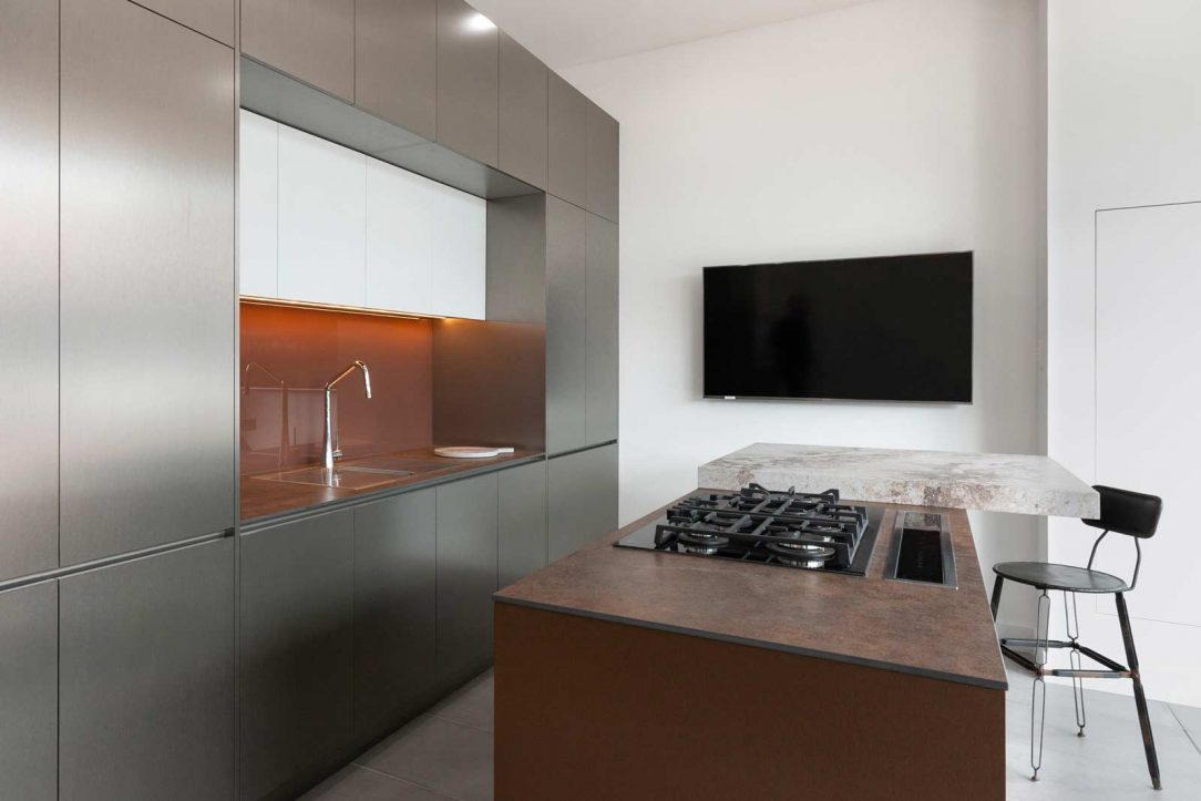 Modern kitchen design featuring Caesarstone Excava and Neolith Iron Corten benchtop and metallic cabinet finish
