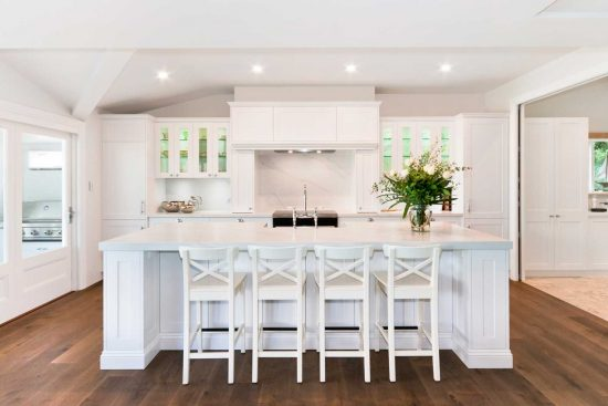 Classic style kitchen design featuring Dulux Vivid White polyurethane shaker doors, Miele & Smeg appliances, Essastone Calacatta benchtop and stylish butler sink. Also features separate butlers pantry and outdoor built-in BBQ.