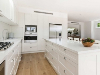 White Hamptons style kitchen featuring Fisher & Paykel and Miele appliances, Quantum Quartz stone benchtop in Michelangelo and Franke sink.