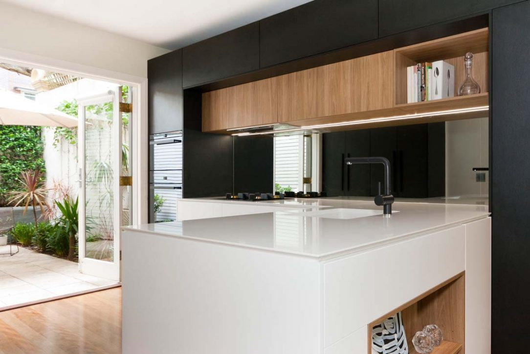 Modern kitchen design featuring Quantum Quartz Alpine White stone benchtop with Sharknose profile. Cabinets in Polytec Black and Prime Oak Woodmatt and Dulux Lexicon polyurethane in satin finish. Also featuring Blum Aventos lift up system for overhead cabinets.