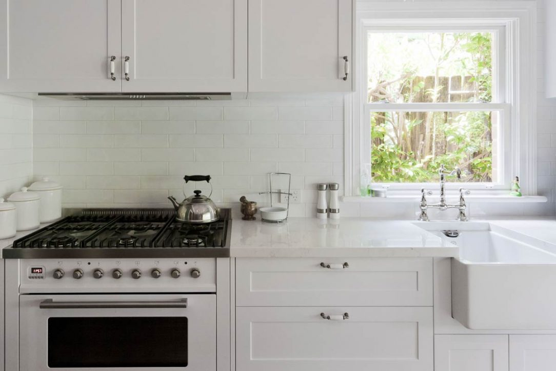 Classic kitchen design featuring Quantum Quartz Michelangelo stone benchtop, Ilve freestanding cooker, butlers sink, french provincial style tapware and handles and white subway tiled splashback.