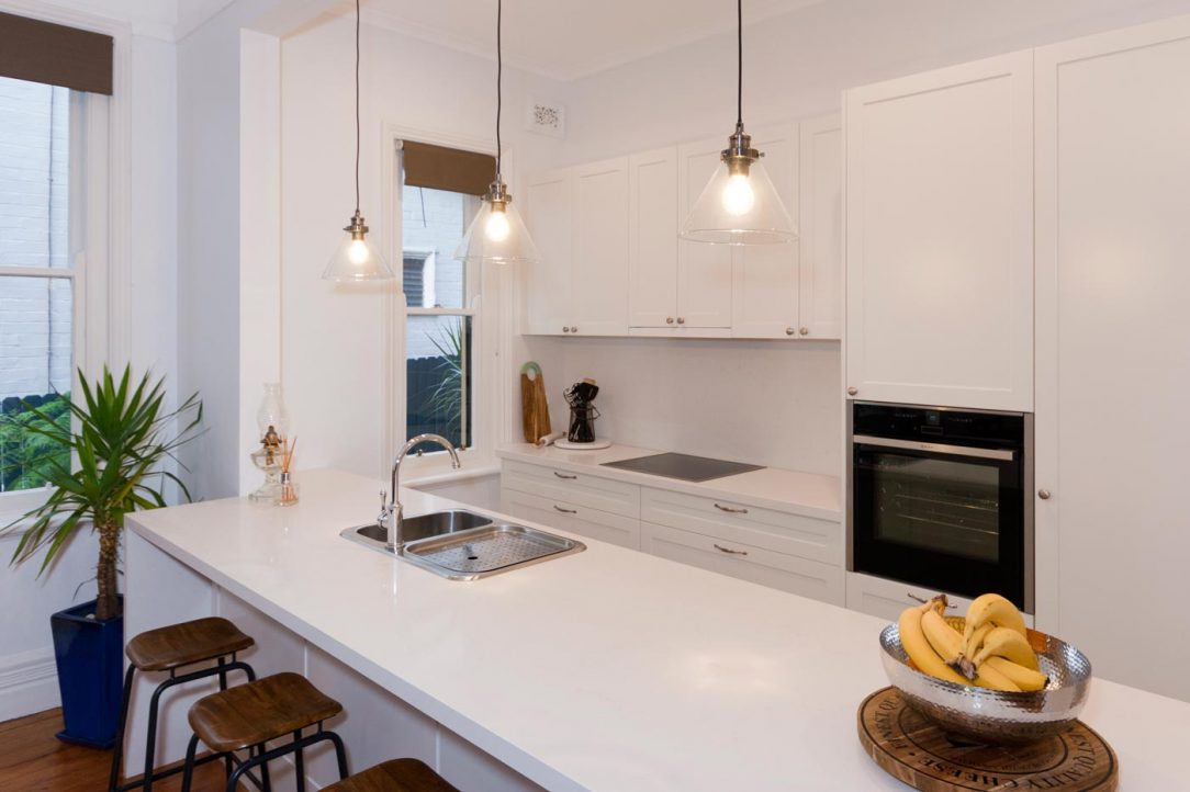 Photo of classic style kitchen design with Caesarstone Frosty Carina stone benchtop, Dulux polyurethane shaker cabinets in Whisper White, Neff Appliances and Astra Walker tapware