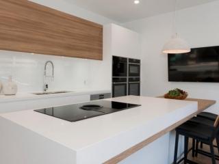 Scandinavian kitchen design featuring Caesarstone Pure White & Neolith La Boheme benchtop, Dulux Whisper White poly and timber veneer doors, Elica & Neff appliances, Clark sink & Abey tapware. Designed by Premier Kitchens Australia.