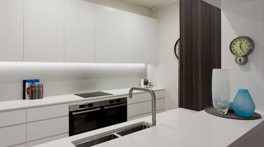 Photo of modern galley kitchen design featuring Caesarstone Snow benchtop, Dulux polyurethane cabinets, Miele, Bosch and Neff appliances and Pete Evans sink and mixer.