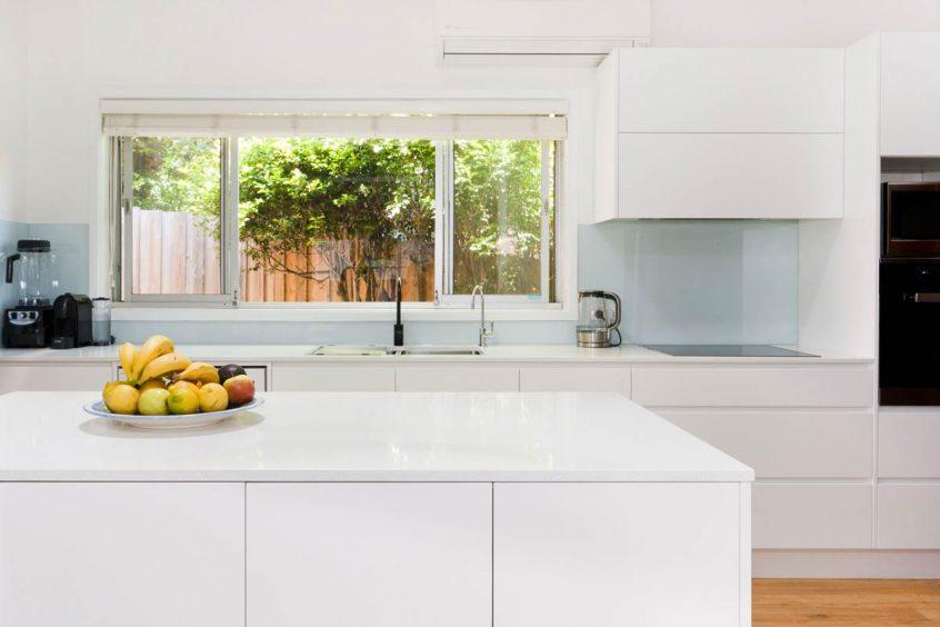 Modern minimalistic kitchen design featuring Caesarstone Ocean Foam stone benchtop and Miele appliances. Kitchen renovation by Premier Kitchens Australia.