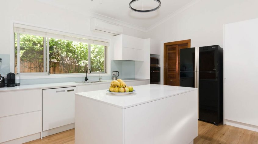 Modern minimalistic kitchen design featuring Caesarstone Snow stone benchtop and Miele appliances. Kitchen renovation by Premier Kitchens Australia.