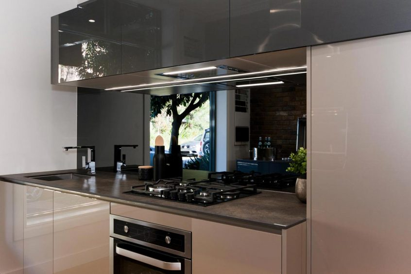 Contemporary compact kitchen design, Neolith benchtop, high gloss finish, dark palette, mirror splashback