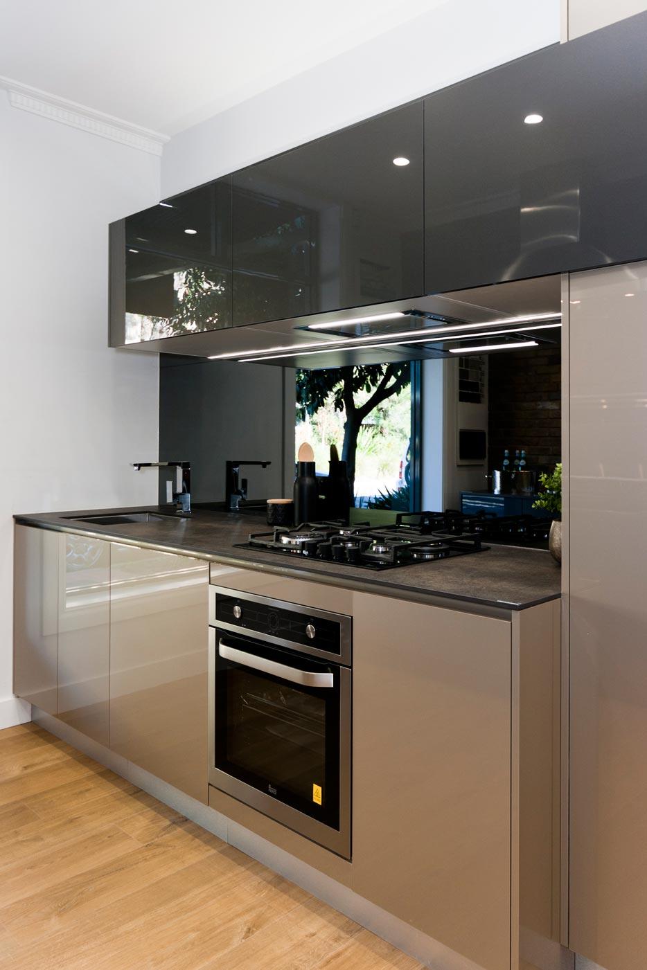 Contemporary compact kitchen design, Neolith benchtop, high gloss finish, dark palette, mirror splashback