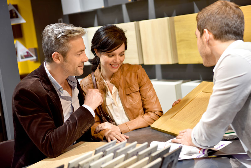 couple talking to kitchen designer at kitchen design showroom display