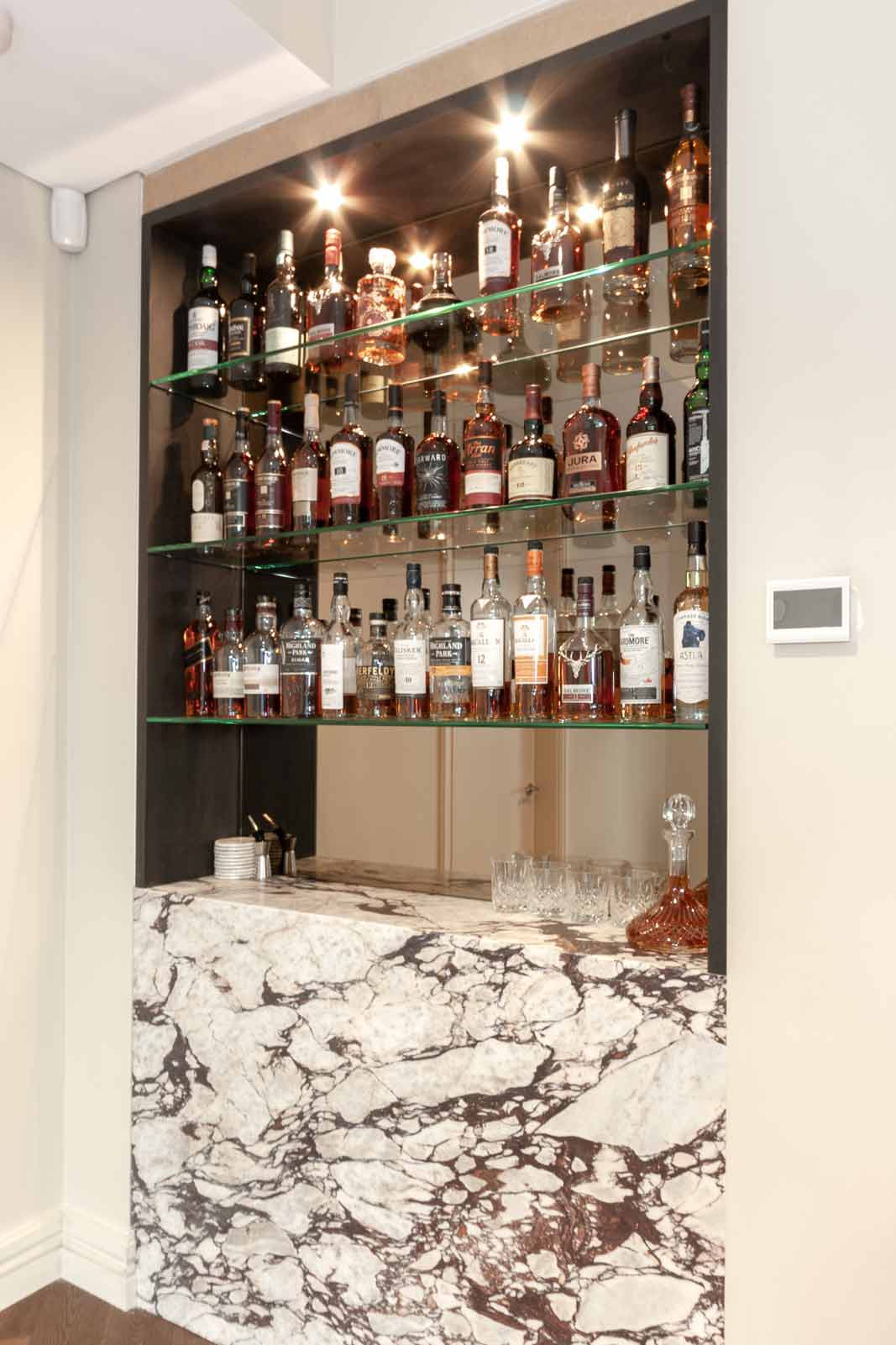 Custom shelving liquor cabinet design with natural stone counter and glass shelves
