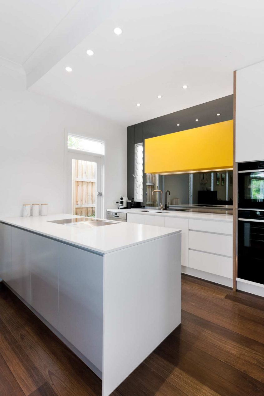 Modern kitchen design Sydney, featuring Dulux polyurethane cabinets in white, grey, yellow and Polytec timber grain feature. Also featuring Silestone white benchtop, Clark sink and Bora downdraft cooktop.