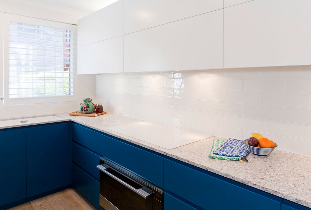 Modern blue and white kitchen design featuring Caesarstone Blanco Drift stone benchtop, Dulux polyurethane kitchen cabinets and Smeg cooking appliances.