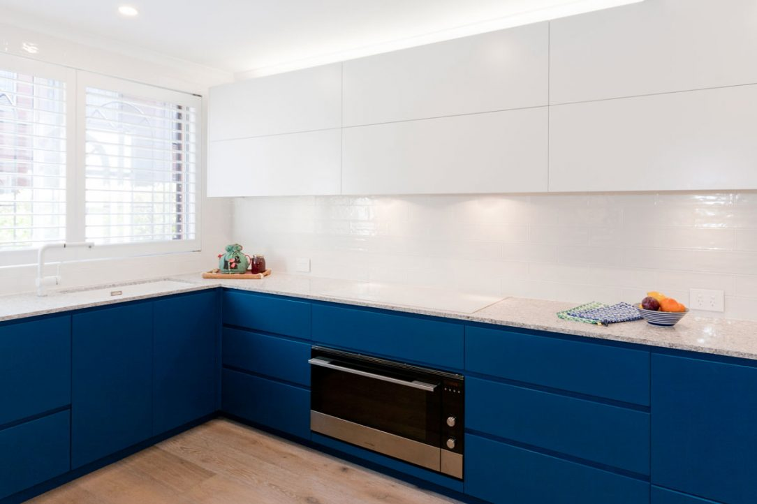 Contemporary kitchen design renovation featuring Fisher & Paykel and Smeg appliances, Caesarstone Blanco Drift stone benchtop, Dulux blue & white polyurethane kitchen cabinets with no handles