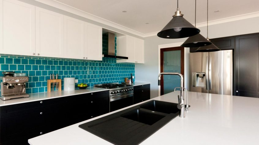 art deco kitchen design after renovation black and white polyurethane joinery with turquoise blue subway tiles splashback