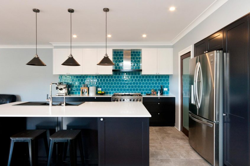 modern art deco kitchen design after renovation black and white polyurethane joinery with turquoise blue subway tiles splashback