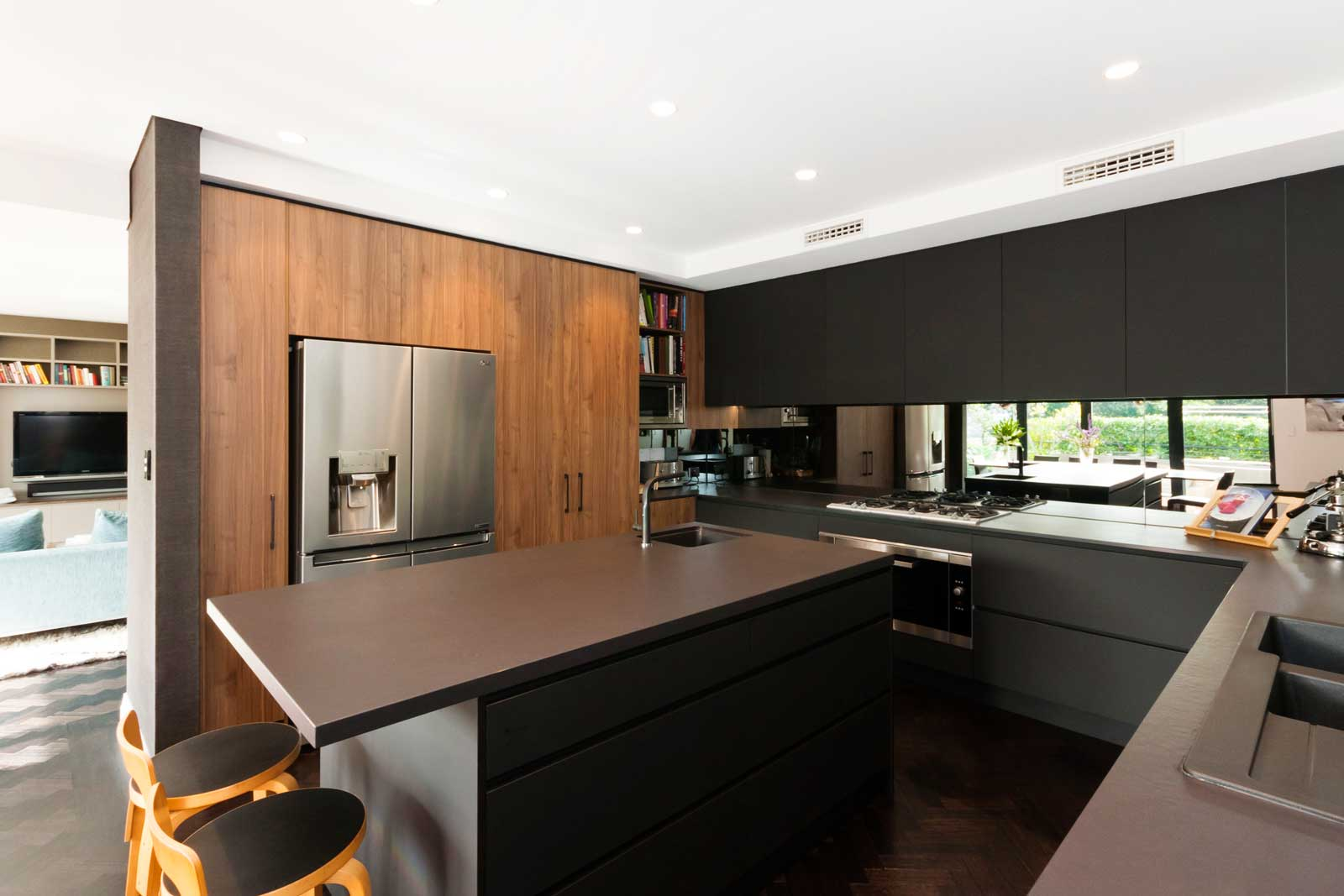 Black & walnut kitchen design featuring Miele cooking appliances, Miele dishwasher, LG fridge, Sirius rangehood, Blanco microwave, Blum cabinet hardware, Abey sink & mixer, Franke sink & mixer and Dekton Sirius benchtop.
