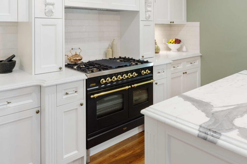 Kitchen design classic French provincial style detailing with Dulux white polyurethane shaker doors, Ilve freestanding cooker and large butlers sink with brass tapware and cabinet handles.