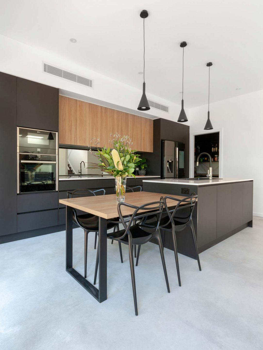 Black & timber kitchen design featuring Matt Blatt chairs, Samsung fridge, Silestone benchtop & Abey sink. Designed by Premier Kitchens Australia.