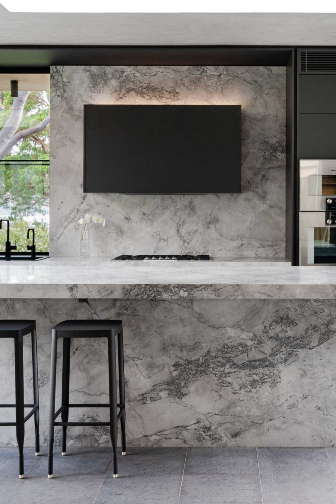 Luxury kitchen design featuring superwhite natural stone, Gaggenau appliances and hidden butlers pantry
