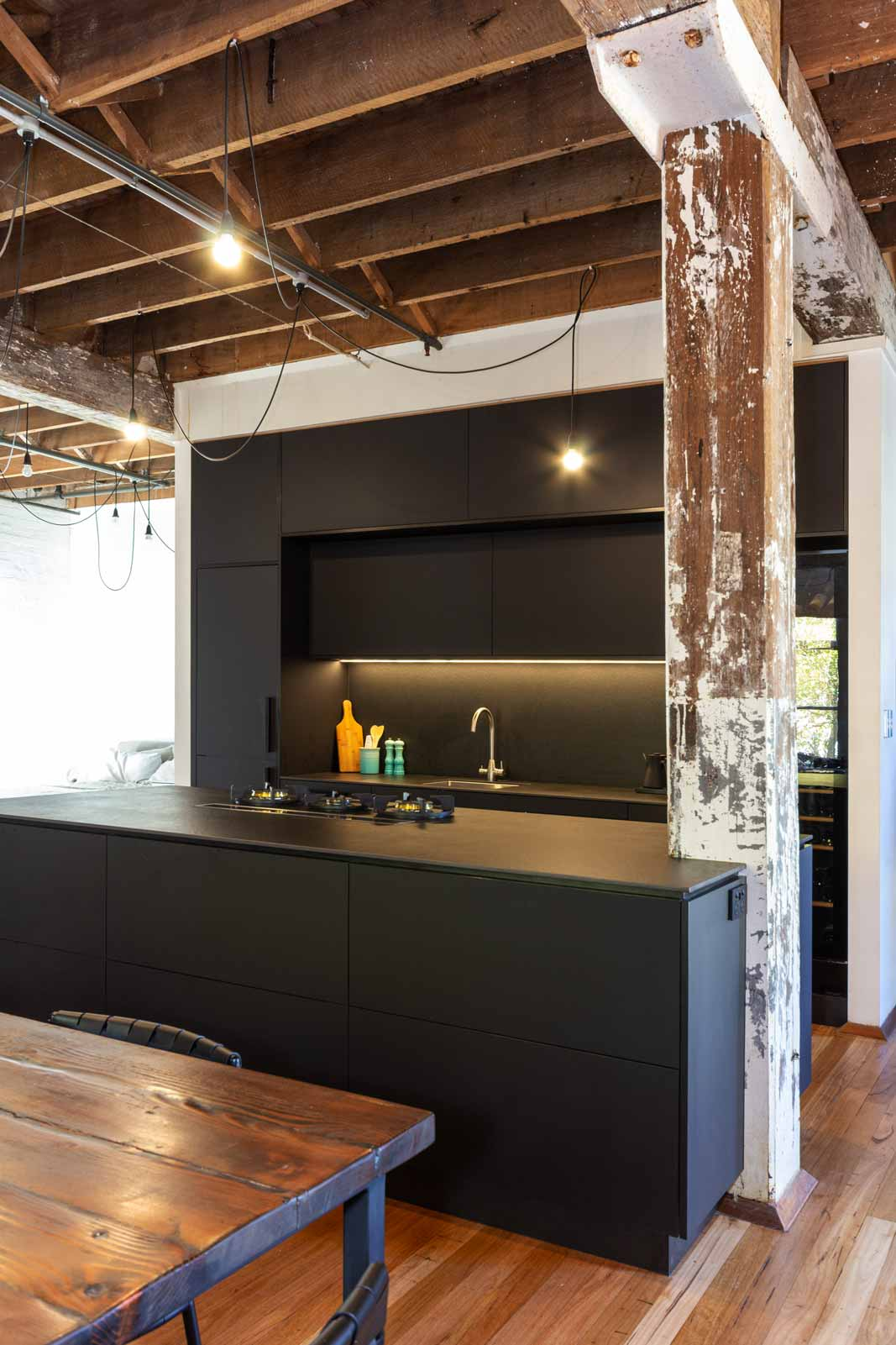 Matt black luxury industrial kitchen design featuring Bosch oven, Vintec wine fridge, Franke sink, Pitt gas burners, Elica downdraft and Neolith benchtop and splashback