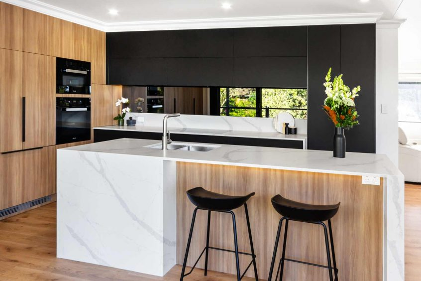 Contemporary black, white and timber kitchen design featuring Miele appliances and Smart Stone Borgini Naturale benchtop