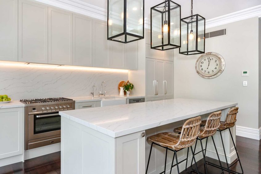 White hamptons style kitchen design featuring Ilve freestanding cooker Smart Stone Calacatta Blanco benchtop and butlers sink