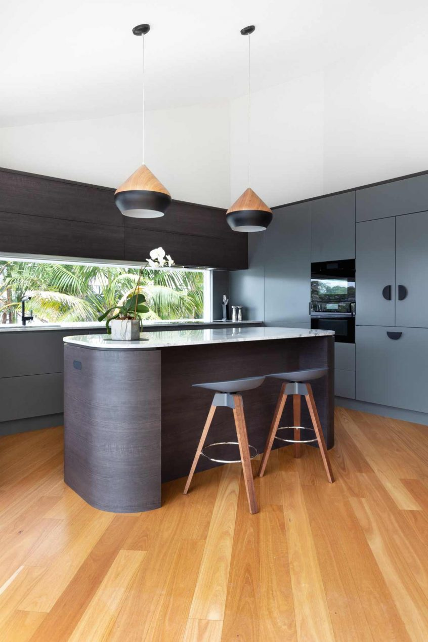 modern luxury kitchen design in Seaforth, Sydney featuring Miele appliances, Blum lift-up overhead cabinets, fully integrated appliances and curved island with stone benchtop. Designed by Premier Kitchens Australia