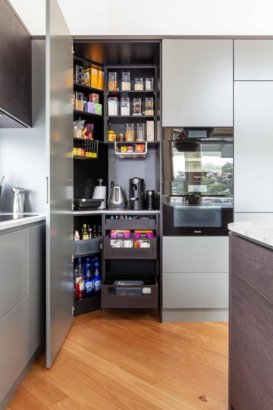 modern luxury kitchen design in Seaforth, Sydney featuring Miele appliances, walk-in pantry small appliance cupboard, Blum lift-up overhead cabinets, fully integrated appliances and curved island with stone benchtop. Designed by Premier Kitchens Australia