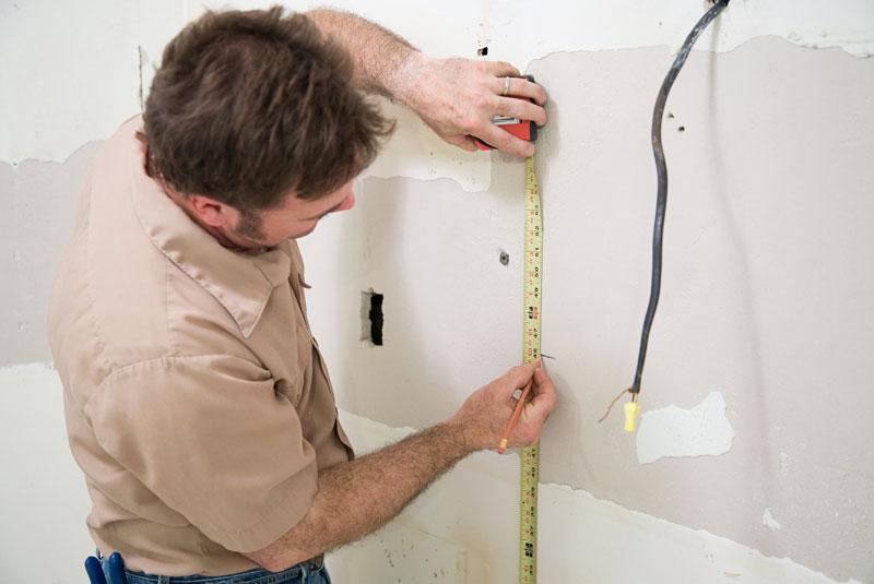 kitchen designer measuring wall for new kitchen installation