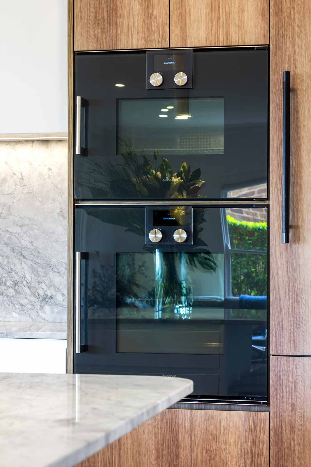 luxury kitchen design by Premier Kitchens featuring Gaggenau appliances, Vintec wine fridge, natural marble benchtop and splashback.