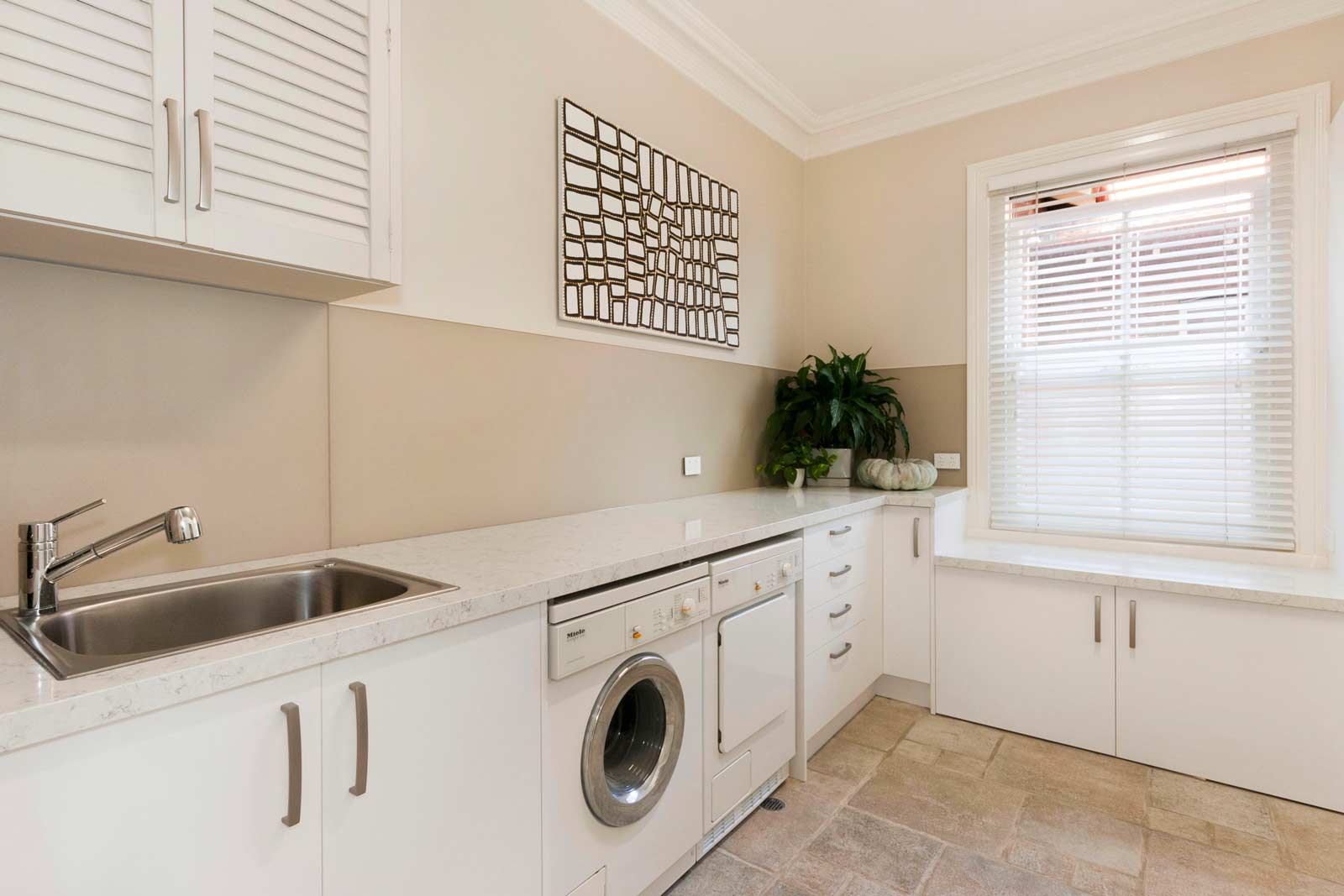 Modern laundry design featuring Miele appliances, Silestone quartz bench top in Blanco Orion, white laminate doors, a second fridge & plenty of extra storage