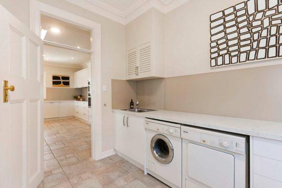 Modern laundry design featuring Miele appliances, Silestone quartz bench top in Blanco Orion, white laminate doors, a second fridge & plenty of extra storage