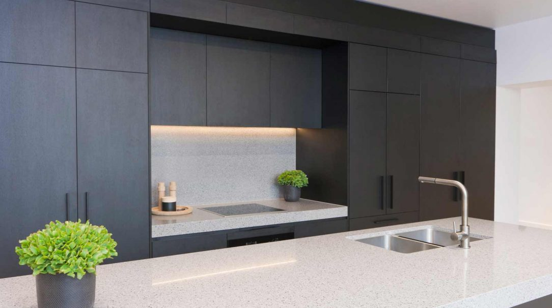Modern, matte black timber grain kitchen design featuring fully integrated Fisher & Paykel french door fridge/freezer, concealed laundry, Miele cooking appliances, integrated Miele dishwasher, Franke sink & mixer and Silestone Chrome benchtop