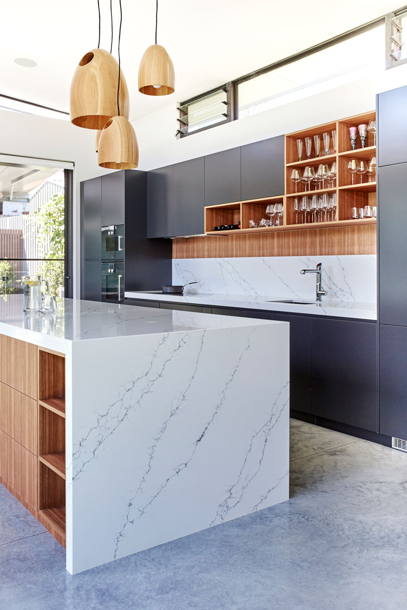 Modern kitchen design featuring quantum quartz venatino statuario benchtop, gaggenau appliances, navurban timber veneear and dulux polyurethane domino black cabinets plus a stunning polished concrete floors. Kitchen designed by Premier Kitchens Australia.