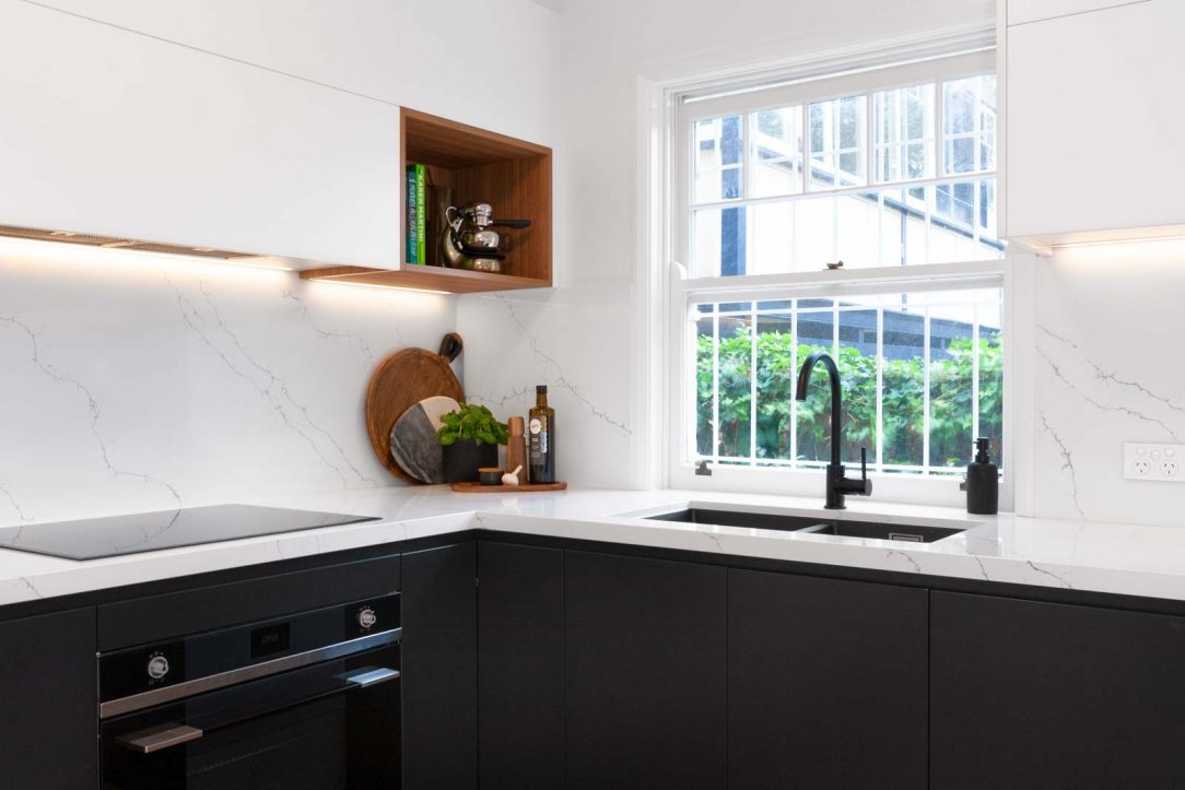 Modern black & white kitchen design with warm timber accents, featuring Smeg appliances, Fisher & Paykel Fridge, Dulux polyurethane doors, Quantum Quartz benchtop, black Blanco sink & black tapware.