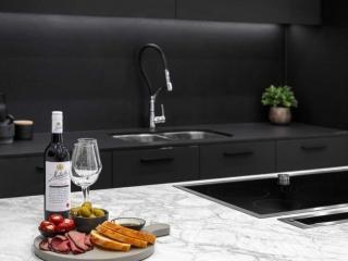 Modern kitchen design with black cabinets, white Dekton Portum benchtop, black Neolith splashback, Elica downdraft and Neff induction cooktop.