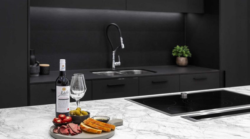 Modern kitchen design with black cabinets, white Dekton Portum benchtop, black Neolith splashback, Elica downdraft and Neff induction cooktop.