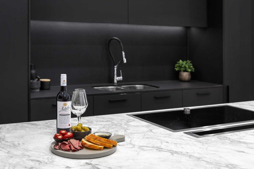 Modern kitchen design featuring Dekton Portum benchtop, black cabinets, black Dekton splashback, Elica downdraft and Neff induction cooktop.