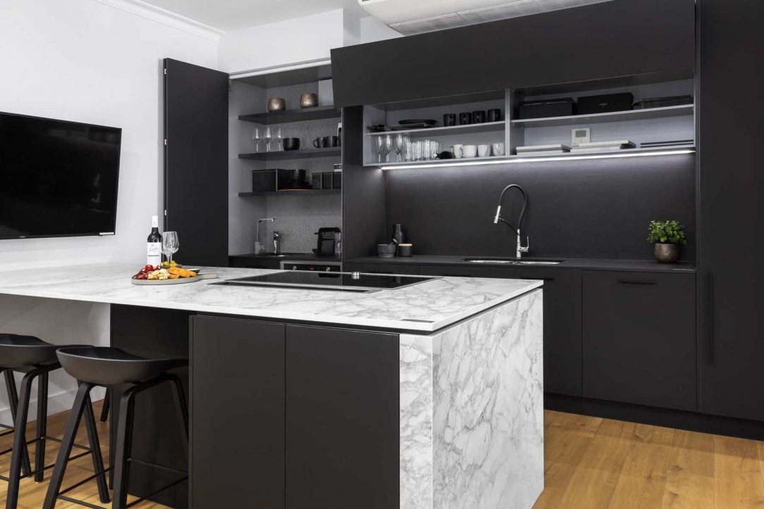Modern kitchen design featuring Dekton Portum benchtop, black cabinets, black Neolith splashback, Elica downdraft and Neff induction cooktop.