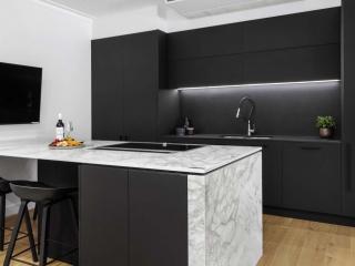 Modern kitchen design featuring Dekton Portum benchtop, black cabinets, black Neolith splashback, Elica downdraft and Neff induction cooktop.