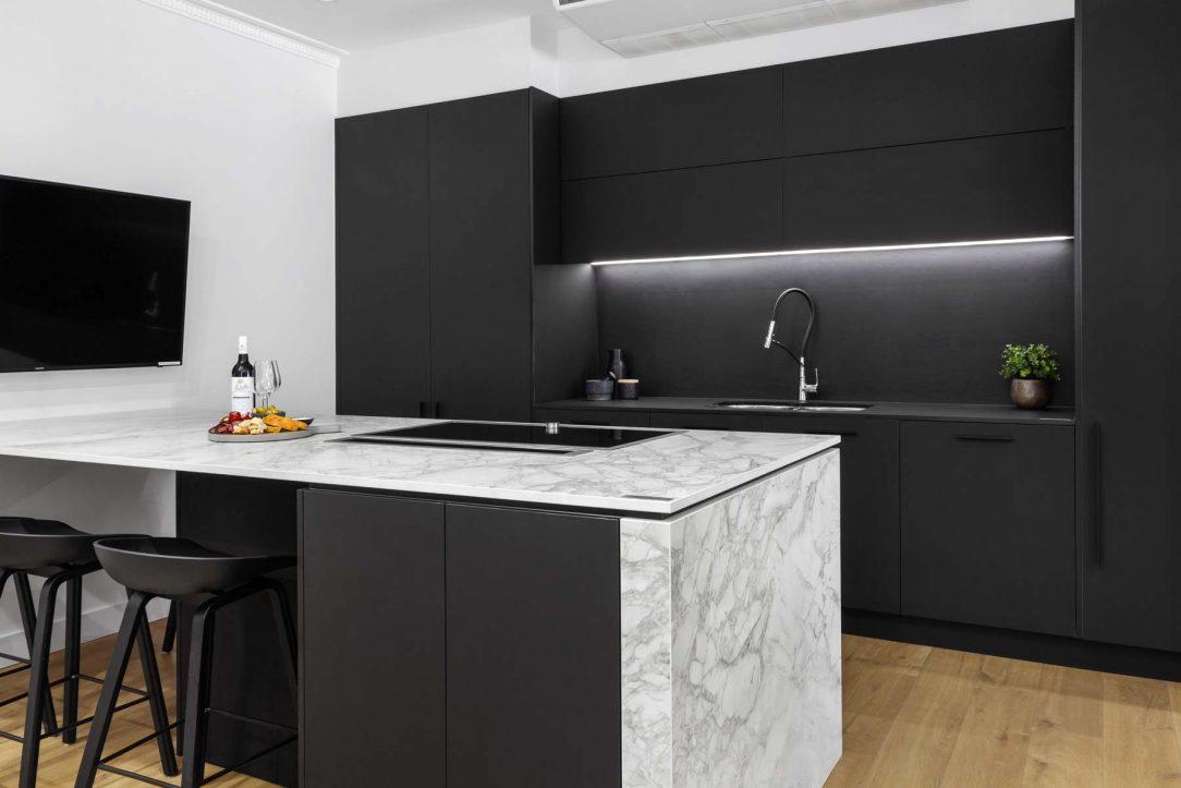 Modern kitchen design featuring Dekton Portum benchtop, black cabinets, black Dekton splashback, Elica downdraft and Neff induction cooktop.