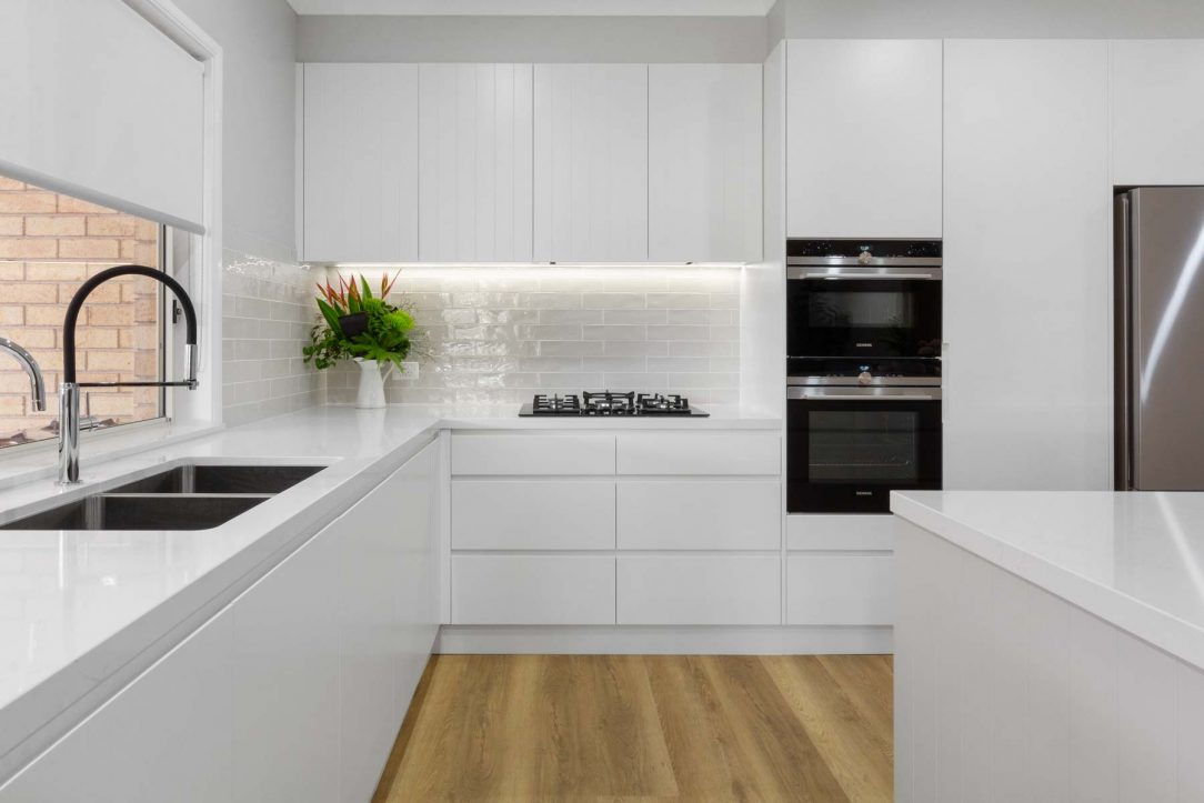 Modern white kitchen design by Premier Kitchens Australia with Dulux polyurethane cabinets and Silestone Eternal Statuario benchtop. Also featuring Bosch gas cooktop, Fisher Paykel fridge, Siemens oven, Zip tap, Oliveri sink and Elica hidden rangehood.
