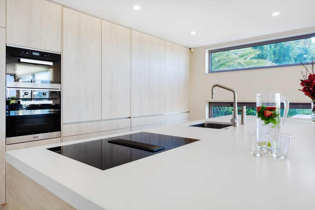 Sandy beech kitchen design with white stone benchtop and flush mount cooktop with downdraft designed by Premier Kitchens Australia