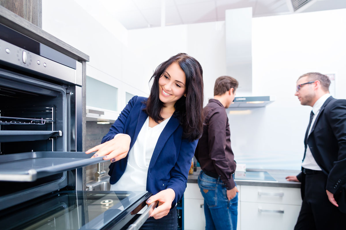 young woman in kitchen design showroom looking at kitchen cabinets and appliances