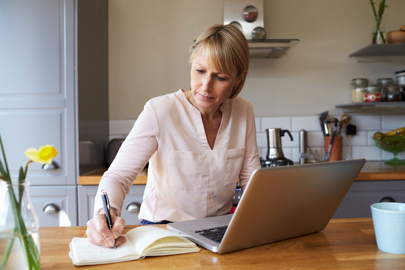 woman writing wish list for new kitchen renovation design